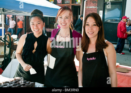 three smiling pretty multiethnic young women selling desserts at specialty stand at Ninth Avenue International Food - Stock Photo