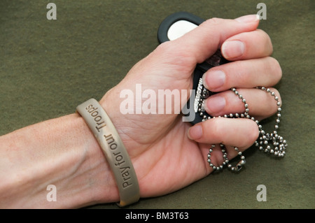 Woman's hand holds military identification 'dog' tags.  She wears a wristband with words in support of troops. - Stock Photo