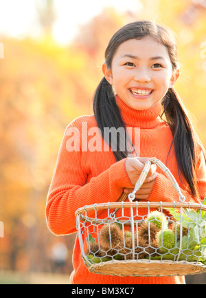 Portrait of Girl Holding Chestnuts Basket, Autumn Color Trees in the Background - Stock Photo