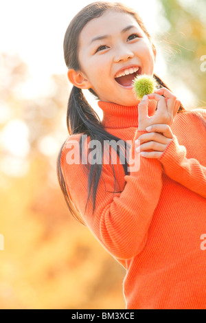 Portrait of Girl Holding Chestnut, Autumn Color Trees in the Background - Stock Photo