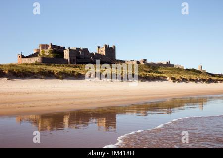 Bamburgh Castle reflected in wet sand on quiet empty beach on Northumbrian coast. Bamburgh Northumberland England UK. Stock Photo
