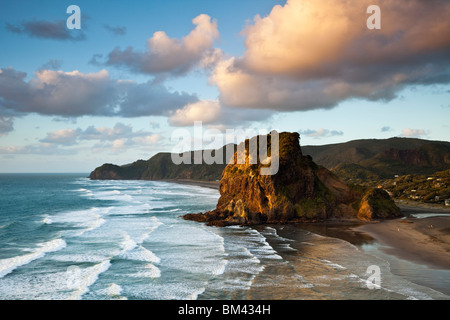 Piha beach and Lion Rock at dusk. Piha, Waitakere Ranges Regional Park, Auckland, North Island, New Zealand - Stock Photo