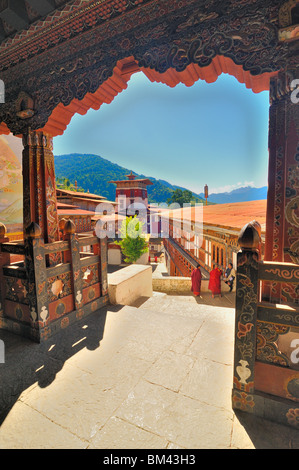 View from temple over courtyard with monks and man in national dress, Trongsa Dzong, Bhutan. - Stock Photo