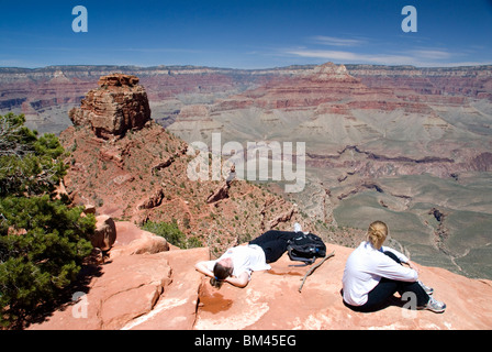 Two hikers resting at Cedar Ridge on the South Kaibab Trail south rim Grand Canyon National Park Arizona USA - Stock Photo