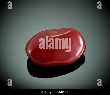 Cutout of a Red Jasper gemstone on black background - Stock Photo
