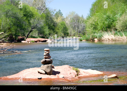 Pebbles arranged as standing stone sculptures at Oak Creek River in Red Rock State Park just outside Sedona Arizona - Stock Photo