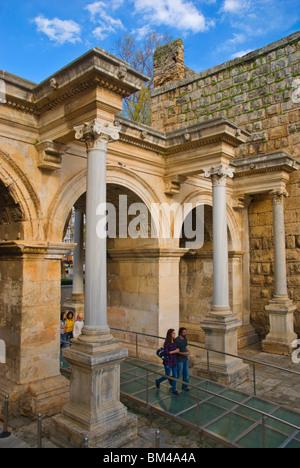 Couple walking through Hadrian's Gate at Kaleici old quarter Antalya Mediterranean coast Turkey Asia - Stock Photo