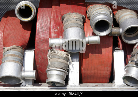Coiled fire hoses ready for use on a fire engine. - Stock Photo