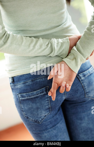 Woman with fingers crossed behind her back - Stock Photo