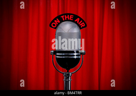 Retro microphone on stage against a red curtain with spotlight effect - Stock Photo