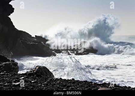 Heavy Atlantic seas with large waves crashing onto the beach at Ajuy on the Canary Island of Fuerteventura - Stock Photo