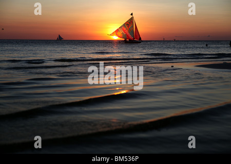 A sail boat passes the sunset on White Beach, Boracay, the most famous tourist destination in the Philippines. - Stock Photo