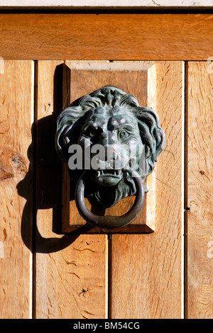 A Lions Head Door Knocker on an exterior Wooden Door in the village of Sutton Veny near Warminster Wiltshire United - Stock Photo