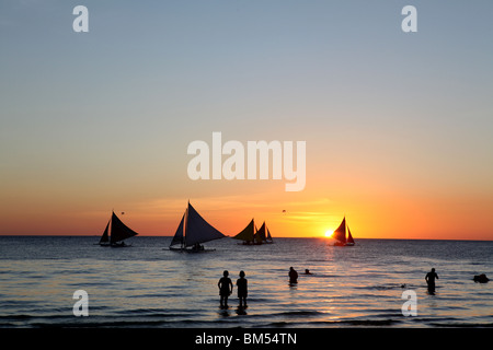 Sail boats ply the shore line at sunset on White Beach, Boracay, the most famous tourist destination in the Philippines. Stock Photo