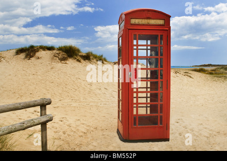 Traditional red British telephone box still in service on the coastal sand dunes of Studland Peninsula, Dorset England - Stock Photo