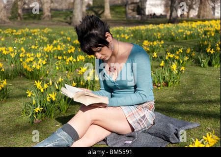 Young woman reading a book in St James's Park, London, England, UK - Stock Photo