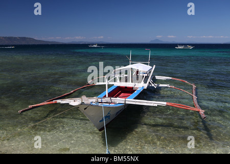 Boat moored off Small La Laguna Beach in Puerto Galera, located on the north of Mindoro Occidental in the Philippines. - Stock Photo