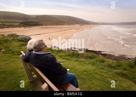 UK, England, Devon, Woolacombe, holidaymakers sitting on bench above the beach - Stock Photo