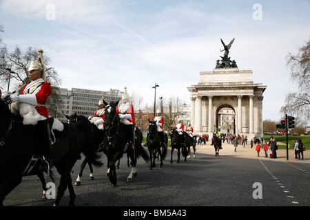 Household Cavalry ride through Wellington Arch, Hyde Park Corner, on their way to the Changing the Guard ceremony, - Stock Photo