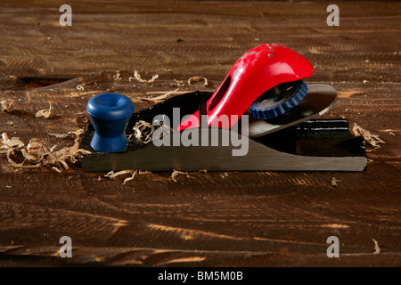 planer carpenter hand tool wood shaving over wooden board - Stock Photo