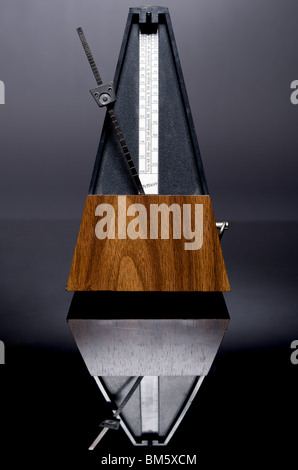 Photo of wooden clockwork metronome with bar-marking bell, ticking, with reflection in black perspex - Stock Photo