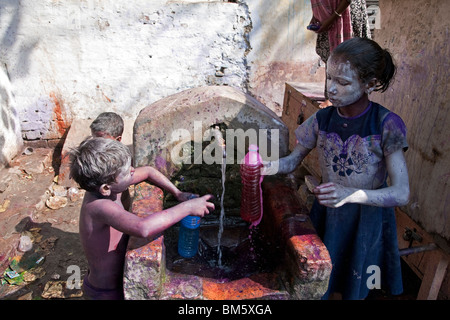 Girl filing a bottle with water and dyes. Holi festival. Varanasi. India - Stock Photo