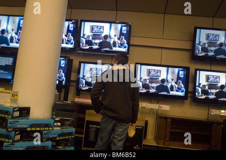 Customers browse the flat screen television display at a Best Buy electronics store in New York - Stock Photo