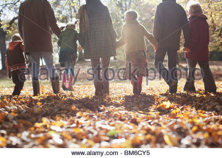 Extended family holding hands and walking outdoors - Stock Photo