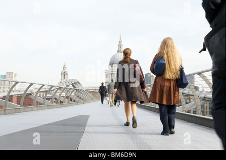 People walking on Millennium Bridge towards St Paul's Cathedral in London - Stock Photo