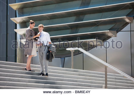 Business people walking down steps outdoors - Stock Photo