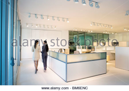 Businesswomen walking together in office - Stock Photo
