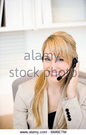 Smiling businesswoman wearing headset in office - Stock Photo
