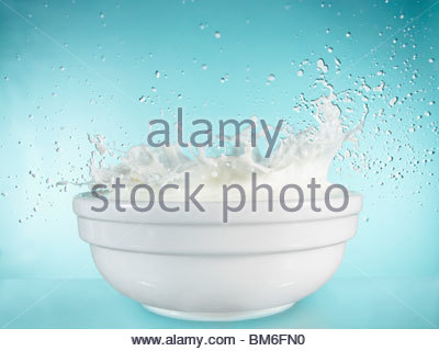 Close up of milk splashing out of bowl - Stock Photo
