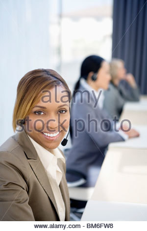 Businesswoman wearing headset at desk in office - Stock Photo