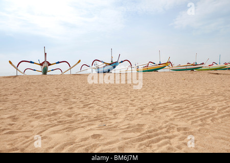 Traditional outrigger fishing boats on the beach at Sanur, Bali, Indonesia - Stock Photo