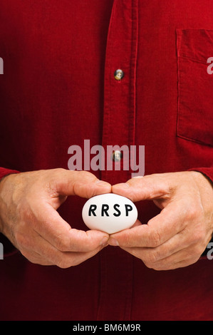 Man holds egg with RRSP written on it - a registered retirement savings plan in Canada - Stock Photo