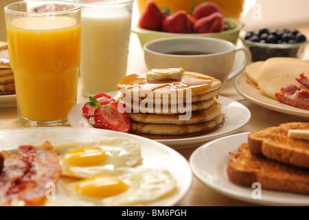 Breakfast pancakes, fruit, eggs, bacon and toast - Stock Photo