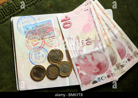 Turkish 90 day multiple entry visa in UK passport with entry and exit stamps and coins and Turkish Lire banknotes - Stock Photo