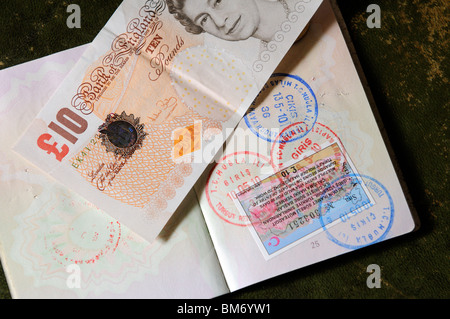 Turkish 90 day multiple entry visa in UK passport with entry and exit stamps. Tourists to Turkey must pay ten pounds - Stock Photo