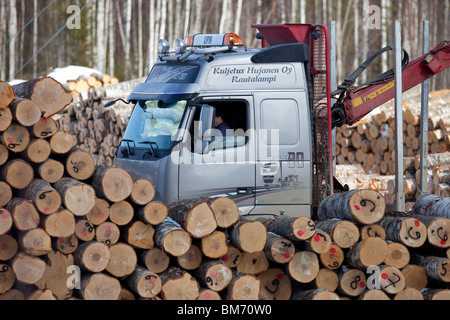 Finnish logging truck and driver driving between log piles in log yard , Finland