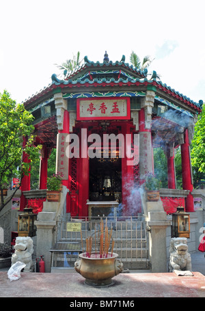 Incense burning in front of the red doorway and lion steps of the Buddhist Yue Hing Shrine, Wong Tai Sin Temple, - Stock Photo