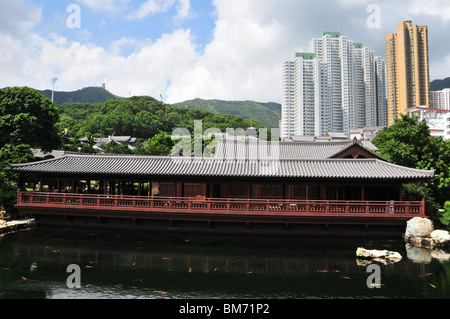 Blue Pond with golden carps in front of the Tang Style Pine Teahouse, Chi Lin Nunnery, Kowloon, Hong Kong, China - Stock Photo