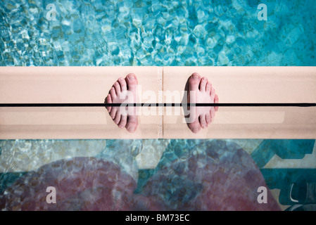 someones feet on the edge of a swimming pool against glass with a reflection making twin feet - Stock Photo