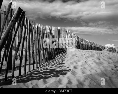 sand dunes at Formby Point Near Liverpool on the Merseyside coast, showing fence, footprints in the sand in black - Stock Photo