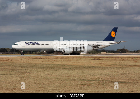 Lufthansa Airbus A340-600 long-haul widebody passenger jet plane lining up on the runway for departure from Malta - Stock Photo