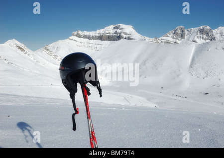 Helmet and ski poles with the back bowls of Lake Louise Ski Resort in the background - Banff National Park, Alberta, - Stock Photo