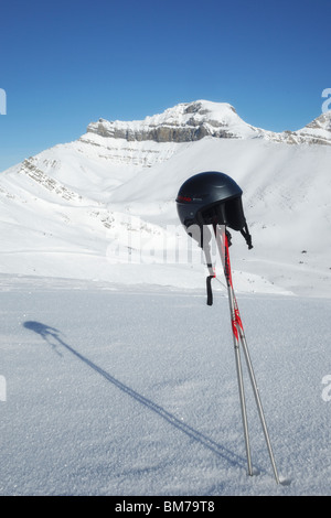Ski poles and helmet with the back bowls of Lake Louise in the background - Banff National Park, Alberta, Canada - Stock Photo