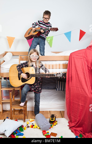 Two children playing with guitars in a child's playroom - Stock Photo