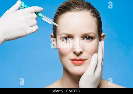 A woman receiving a Botox injection - Stock Photo