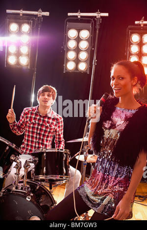 A woman singer accompanied by a man on drums performing on stage - Stock Photo